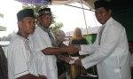 Tampak Bupati menyerahkan bantuan dana bagi panitia pembangunan masjid Annur desa wangga baru Kec Dumoga Barat